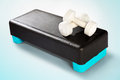 White dumbbells lie on a black-turquoise aerobic step. Royalty Free Stock Photo