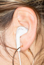 White Earphones in a Girl`s Ear Royalty Free Stock Photo