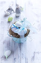 White easter eggs in a nest with blue ribbons an Royalty Free Stock Photos