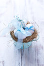 White easter eggs in a nest with blue ribbons an Stock Photography
