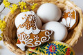 white eggs in wicker nest with decorated gingerbread hen cake with dogwood flower Royalty Free Stock Photo