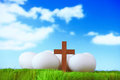 White eggs and wood cross on grass with blue sky Stock Photos