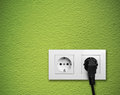 White electric outlet mounted on green wall Royalty Free Stock Photo