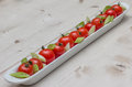 White elongated dish filled with cherry tomatoes and spring onio onions pepper Stock Photography