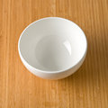 White empty bowl on a bamboo table top Stock Image