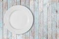 White empty dinner plate on left side of blue wooden table Royalty Free Stock Photo