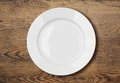 White empty dinner plate on wooden table surface Royalty Free Stock Photo
