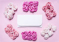 White envelope on a pink background with a tiled around bundles of multicolored roses top view close up place text frame for Royalty Free Stock Image