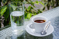White espresso cup with glass of cold water standing on the street cafe table Stock Photo