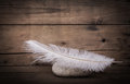 White feather and a stone on wooden dark background for mourning Royalty Free Stock Photo