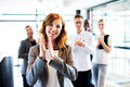 White female executive standing in front of colleagues clapping young and smiling Royalty Free Stock Photography