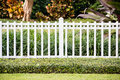 A white fence in front of a representative home cozy and with very well groomed green lawn Royalty Free Stock Image