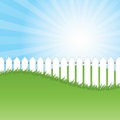 White fence and green grass on blue sky background