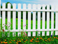 White fence on green grass with flowers. Royalty Free Stock Photo