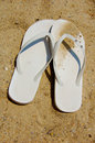 White flip flops in the sand a pair of sandals on a sunny day Royalty Free Stock Images