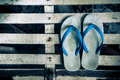 White flip flops Sandals on the floor of an old white wooden in home, Royalty Free Stock Photo