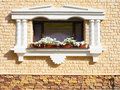 White flowers hangs on the window of a home in an ancient buildi Royalty Free Stock Photo
