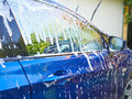 White foam flows down on glass and blue car body. Royalty Free Stock Photo