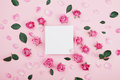 White frame blank, pink rose flowers and petals for spa or wedding mockup on pastel background top view. Beautiful floral pattern.