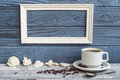 White frame, coffee cup and shells on a background of blue board Royalty Free Stock Photo