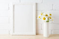 White frame mockup with daisy flower near painted brick wall
