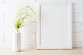 White frame mockup with wild grass ears near painted brick wall Royalty Free Stock Photo