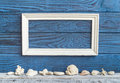 White frame and shells on a background of blue boards Royalty Free Stock Photo