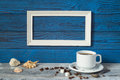 White frame, two coffee cups and a jug on a background of blue b Royalty Free Stock Photo