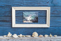 White frame whith foto and shells on a background of blue boards Royalty Free Stock Photo