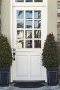 White front door to modern home flanked by plants a a the has glass windows and is two also seen is the stone porch and Stock Images