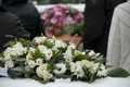 White funeral flowers in the snow before a caket arrangement on hedge at cemetery casket Stock Image