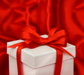 White gift box with red bow ribbon over satin background Stock Image