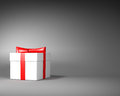 White gift box with red ribbon and bow on the gray background space for text Royalty Free Stock Image