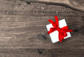 White gift box with red ribbon bow on wooden background over Stock Photo