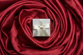 White gift box on red silk Stock Photos