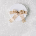 White gift cardboard box with brown bow on concrete background Royalty Free Stock Photo