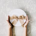 White gift cardboard box with brown bow and girl's hands on concrete background Royalty Free Stock Photo