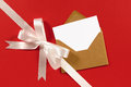 White gift ribbon bow diagonal on red paper background with blank message card and brown envelope and Stock Photos