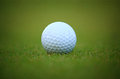 White golf ball on grass with green background photographed in very shallow depth of field Royalty Free Stock Photo
