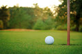 White golf ball on putting green next to hole and flag post with a bunker trees and sunlight in the background Royalty Free Stock Images