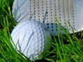 White golf ballcloseup in bright green grass with pitching wedge club face Royalty Free Stock Photo