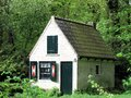 White and green tiny house in green surroundings Royalty Free Stock Photo