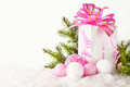 White greeting card with copy space for christmas or new year with a wrapped gift, fir branches and pink ball on snow Royalty Free Stock Photo