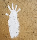 white hand paint prints on dark rough wall