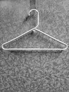 White hanger on coat rack with pattern wall closeup of Royalty Free Stock Images