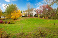 White horse farm american house during fall with green grass northwest ranch changing leaves and fence Stock Images