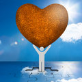 White human representation holding a big brown heart with the sky in background Royalty Free Stock Image
