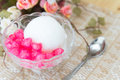 White ice cream made from coconut and pink jelly topping on the photo of table Royalty Free Stock Images
