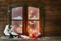 White ice skates and candles at window pane assorted color lighted snowy wooden on christmas season Stock Photo
