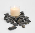 White candle with black stones Royalty Free Stock Photo